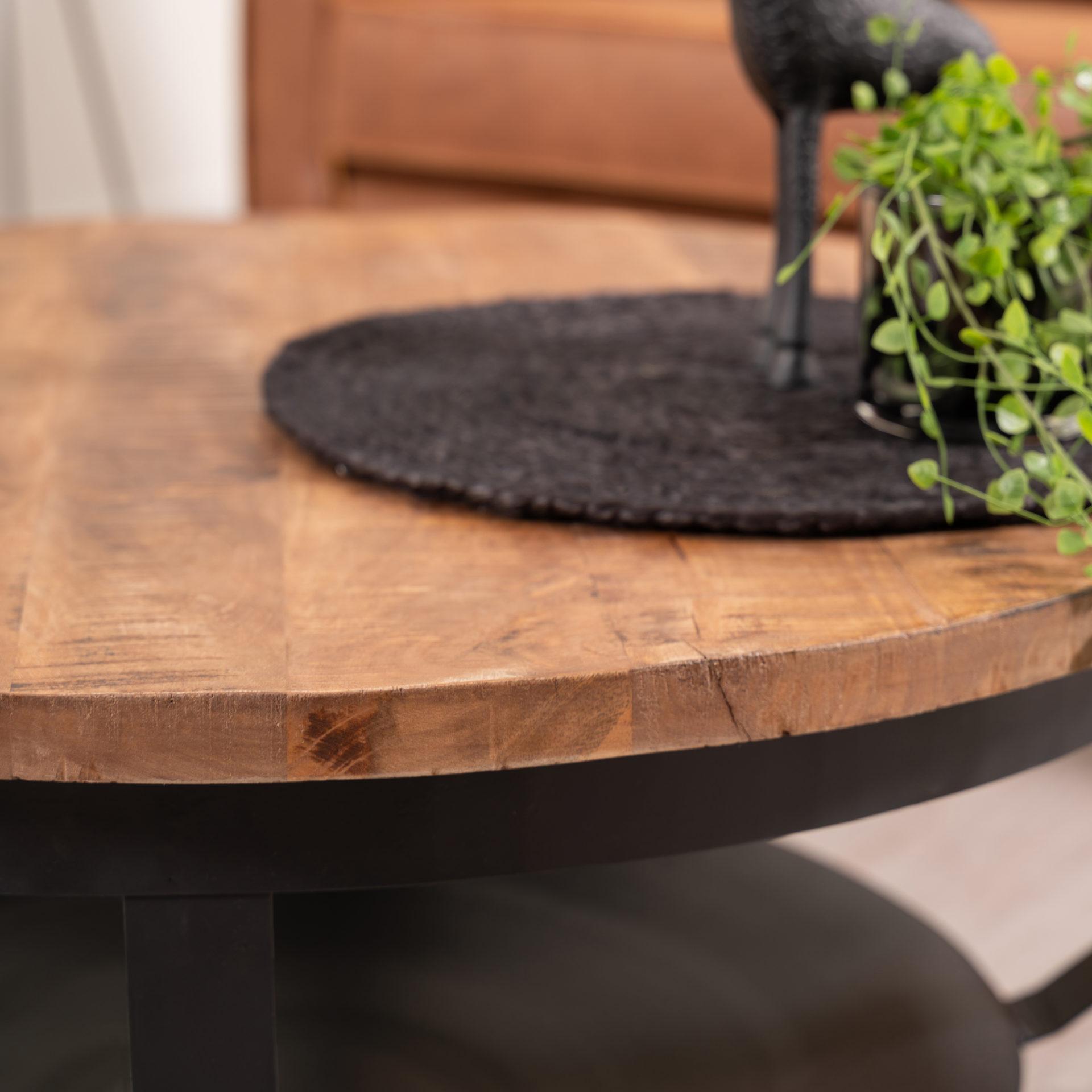 Detailfoto ronde salontafel met houten blad en metalen onderstel