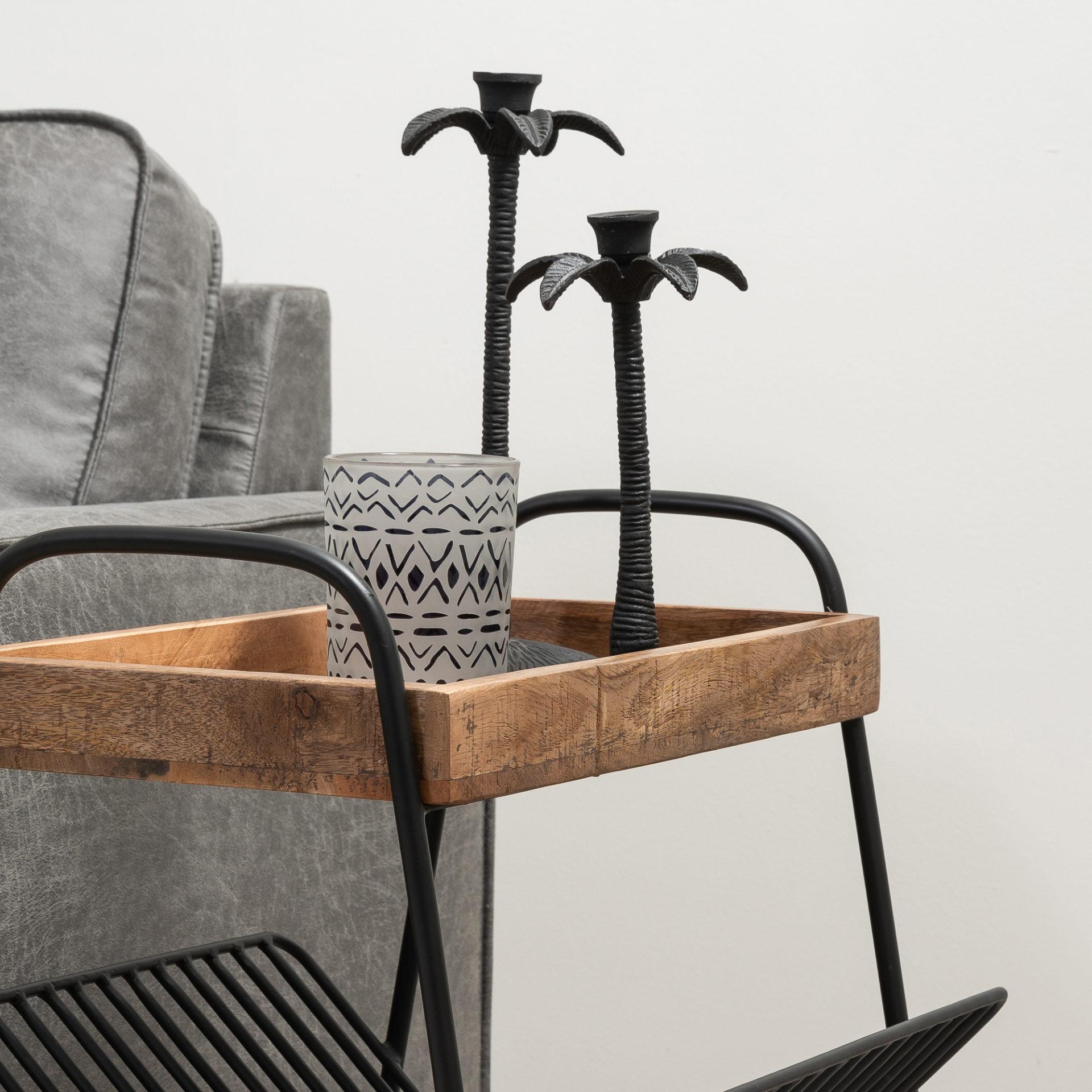 Detailfoto bijzettafel gemaakt van mangohout met metalen onderstel. De tafel beschikt over een plank welke bevestigd zit aan de poot, waar bijvoorbeeld tijdschriften in kunnen.