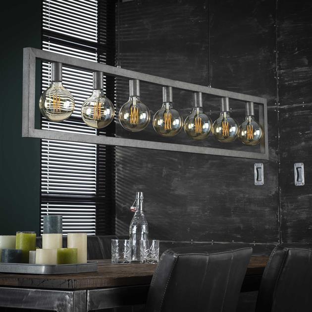 Foto hanglamp met de lampen uit bestaande uit een rechthoekig metalen frame met zeven fittingen voor lichtbronnen. De lamp is afgewerkt in oud zilver en het frame bestaat uit holle metalen buizen waar de stroomkabels doorheen lopen. De lamp is tot 150 cm verstelbaar in hoogte.