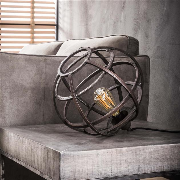 Tafellamp met een bolvormige kap, uitgevoerd in metaal met een antieke koper finish. De lamp heeft geen voetje en ligt dus op zijn kant. De breedte van de lamp is 33 cm en de hoogte 30 cm.