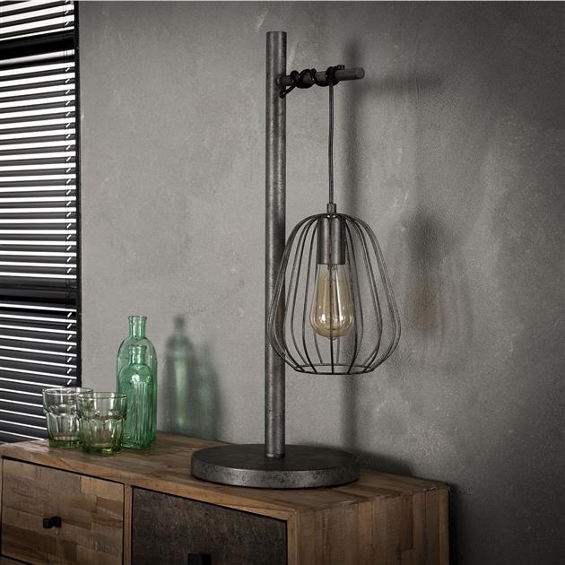Tafellamp van metaal met een oud zilveren afwerking, de kabel komt vanuit de poot aan de zijkant tevoorschijn en is speels om de zijkant heen gedraaid, waaraan de draadstalen lampenkap bungelt. De lamp heeft een hoogte van 66 cm