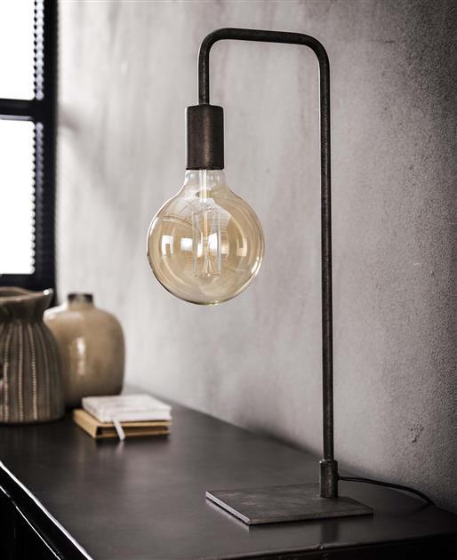 Sfeerfoto slanke en strakke tafellamp afgewerkt in oud zilver. De lamp staat met een vierkant platte voet en heeft een slanke buis. De lamp heeft een hoogte van 50 cm.