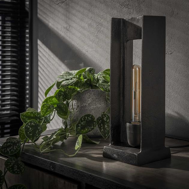 Sfeerfoto metalen tafellamp met een H-figuur met een rechthoekig open vak. De vorm in combinatie met de zwart nikkele afwerking geeft een industriële look. De lamp heeft een hoogte van 37 cm.