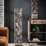 Metalen rechthoekige vloerlamp die is uitgevoerd in een verweerd metalen glazen kap in de kleuren grijs en wit. Het model heeft 3 lichtbronnen die op verschillende hoogtes in de kap aanwezig zijn, verder is de vloerlamp voorzien van een vierkante massieve houten poot. De lamp heeft een hoogte van 110 cm