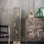 Detailfoto grote metalen rechthoekige vloerlamp die is uitgevoerd in een verweerd metalen glazen kap in de kleuren grijs en wit. Het model heeft 3 lichtbronnen die op verschillende hoogtes in de kap aanwezig zijn, verder is de vloerlamp voorzien van een vierkante massieve houten poot