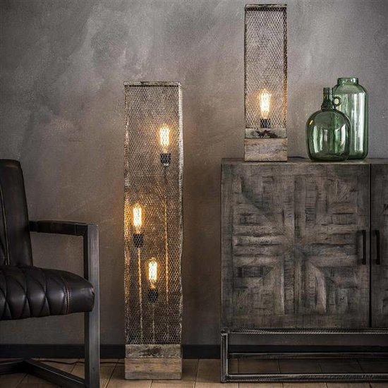 Sfeerfoto metalen rechthoekige vloerlamp die is uitgevoerd in een verweerd metalen glazen kap in de kleuren grijs en wit. Het model heeft 3 lichtbronnen die op verschillende hoogtes in de kap aanwezig zijn, verder is de vloerlamp voorzien van een vierkante massieve houten poot