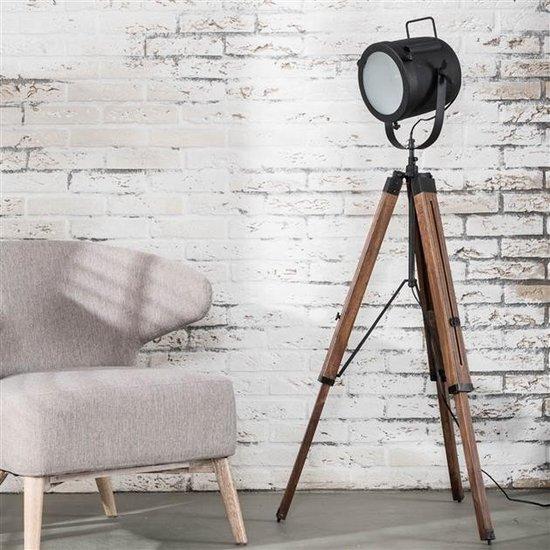 Vloerlamp met de lamp uit met massief houten statief. De kap is voorzien van reflectieglas en is uitgevoerd in ambachtelijk zwart gepoedercoat metaal. De kap is naar beneden te verstellen en tevens in hoogte verstelbaar van 95 tot 135 centimeter.