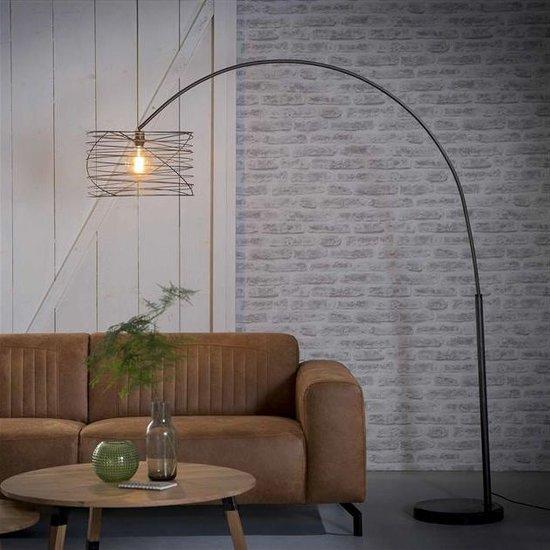 Booglamp met de lamp aan. De lamp heeft een ronde kap in de vorm van een spiraal. De kap en voet zijn gemaakt van metaal in de kleur charcoal, een mat zwarte kleur. De voet is rond en gemaakt van zwart marmer en de lamp heeft een hoogte van 192 cm.