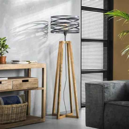 Stijlvolle vloerlamp bij daglicht met een getwiste metalen kap in combinatie met een gekruist houten frame. De kap is afgewerkt met grijs/bruin metaal en de lamp heeft een hoogte van 141 cm.