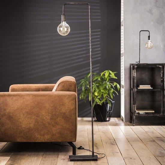Sfeerfoto slanke en strakke vloerlamp afgewerkt in oud zilver. De lamp staat met een vierkant platte voet en heeft een slanke buis en een hoogte van 150 cm.