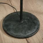 Detailfoto poot van de metalen vloerlamp met ronde conische kap